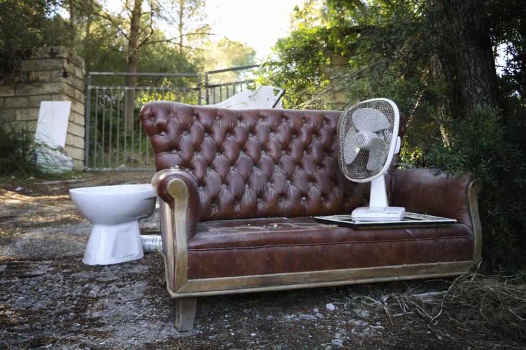 Fotografi som visar en trasig toa, soffa och fläkt.